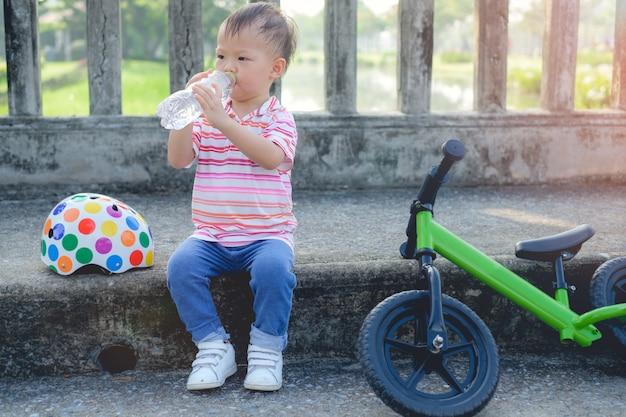Nettes kleines kluges asiatisches 2 jahre altes kleinkindjungenkind, das eine pause macht und reines wasser von der plastikflasche trinkt, nachdem es sein laufrad (laufrad) im park fährt, kind trinkt wasser nach sport. Premium Fotos