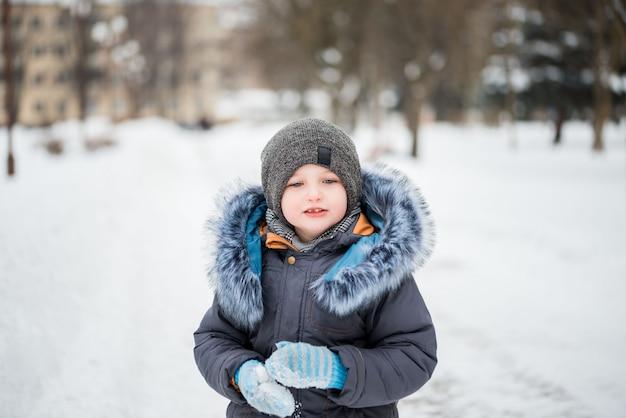 Nettes kleines lustiges kind in der bunten winterkleidung, die spaß mit schnee hat, Premium Fotos