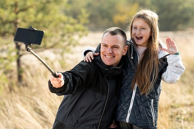 Nettes kleines mädchen, das ein selfie mit ihrem vater nimmt Kostenlose Fotos