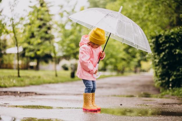 Nettes kleines mädchen, das in einer pfütze in einem regnerischen wetter springt Kostenlose Fotos