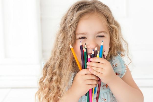 Nettes kleines mädchen, das mit bunten stiften auf papier zeichnet. hübsches kleines kind, das drinnen zeichnet. entzückender künstler. hübsches mädchen, das ihr gesicht mit bleistiften kauert und in die kamera lächelt. Premium Fotos