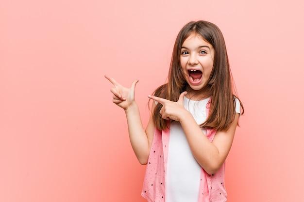 Nettes kleines mädchen, das mit den zeigefingern auf einen kopienraum zeigt, aufregung und wunsch ausdrückt. Premium Fotos