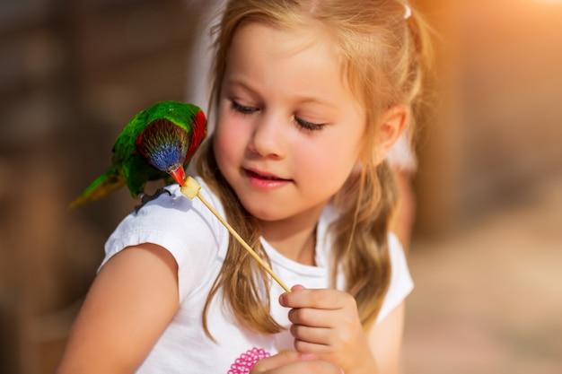 Nettes kleines mädchen, das mit einem papagei spielt und ihn einzieht Premium Fotos