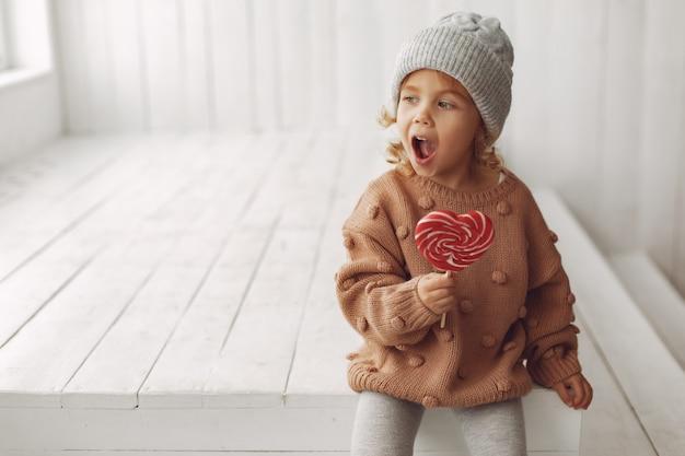 Nettes kleines mädchen, das sitzt und süßigkeiten isst Kostenlose Fotos