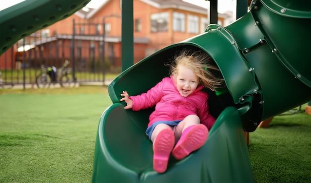 Nettes kleines mädchen, das spaß auf spielplatz im freien hat Premium Fotos