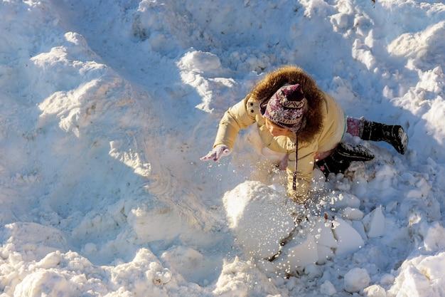 Nettes kleines mädchen, das spaß in den schneefällen hat. kinder spielen draußen wintersaison im schnee. Premium Fotos