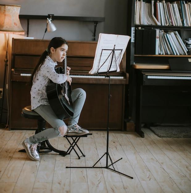 Nettes kleines mädchen, das zu hause auf einer akustikgitarre übt Premium Fotos
