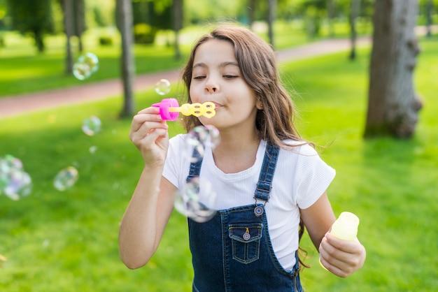 Nettes kleines mädchen der vorderansicht, das seifenblasen macht Kostenlose Fotos
