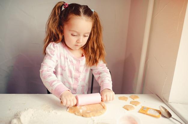 Nettes kleines mädchen haben spaß in einer küche Kostenlose Fotos