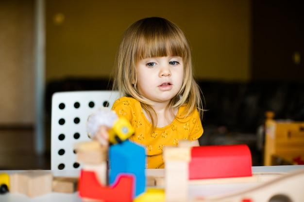 Nettes kleines mädchen im gelben kleid, das mit bunten ziegelsteinen spielt Premium Fotos
