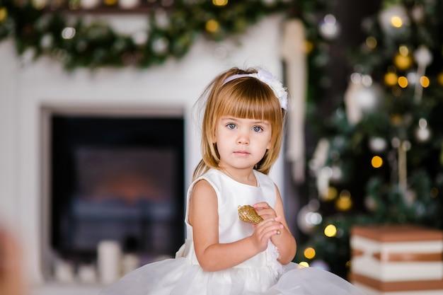 Nettes kleines mädchen im weißen kleid mit nettem kranz nahe dem weihnachtsbaum Premium Fotos
