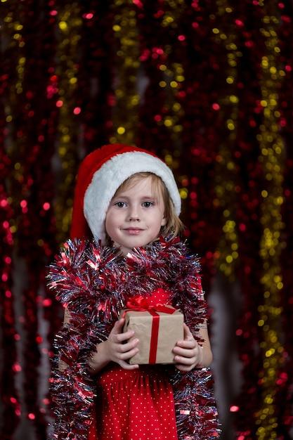 Nettes kleines mädchen in der weihnachtsmütze und mit lametta um ihren hals, der neujahrsgeschenk hält. Premium Fotos
