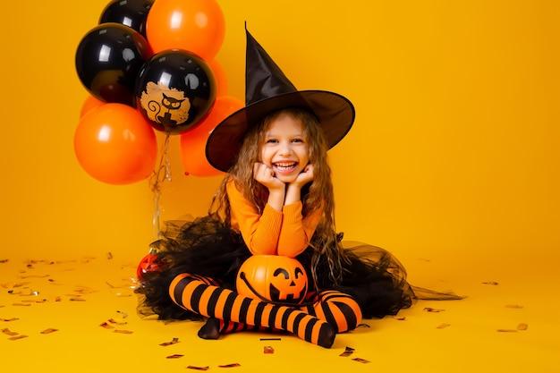 Nettes kleines mädchen in einem hexenkostüm für halloween Premium Fotos