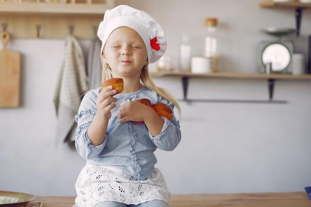 Nettes kleines mädchen in einer küche mit kleinem kuchen Kostenlose Fotos