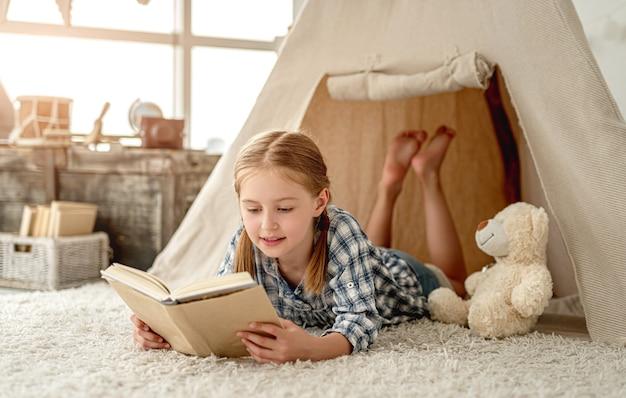 Nettes kleines mädchen mit bär und papierbuch, das auf raumboden sitzt, verziert mit wigwam, brust und retro-laterne Premium Fotos