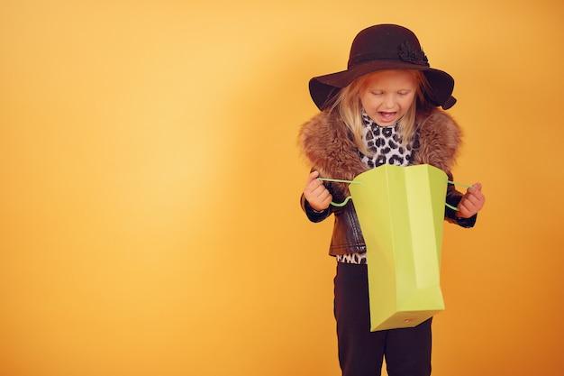 Nettes kleines mädchen mit einkaufstaschen auf einem gelben hintergrund Kostenlose Fotos