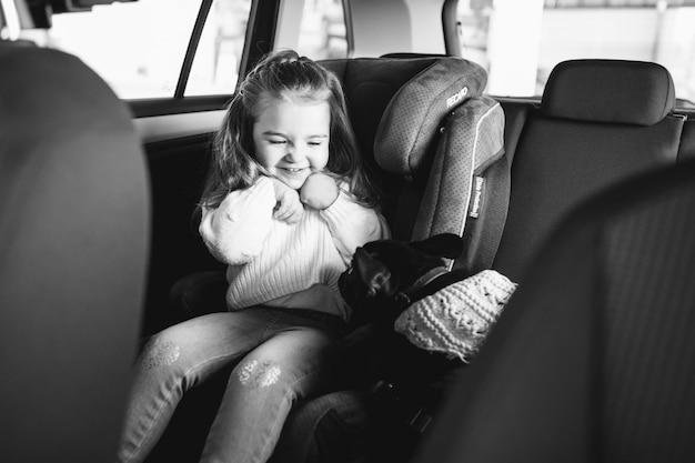 Nettes kleines mädchen mit ihrem haustier, das auf der rückseite eines autos sitzt Kostenlose Fotos