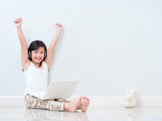 Nettes kleines mädchen mit laptop zu hause Premium Fotos