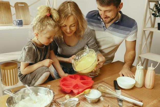 Nettes kleines mädchen und ihre schönen eltern bereiten den teig für den kuchen in der küche zu hause vor Kostenlose Fotos