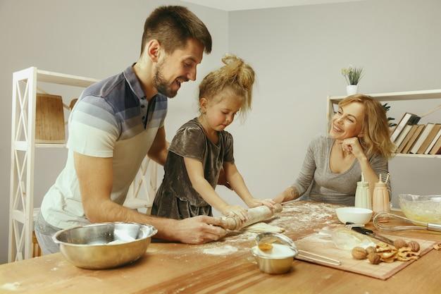 Nettes kleines mädchen und ihre schönen eltern bereiten den teig für den kuchen in der küche zu hause vor. Kostenlose Fotos