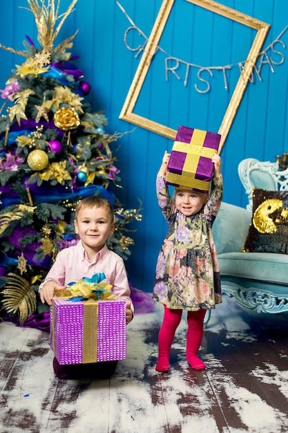 Nettes kleines mädchen und junge lächeln und halten geschenke unter dem weihnachtsbaum Premium Fotos