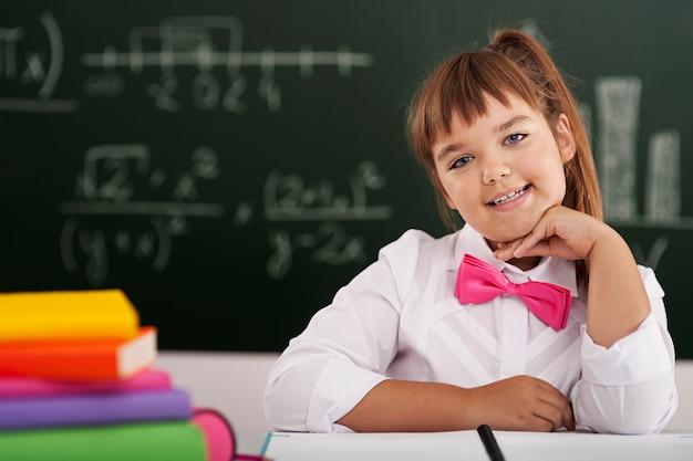Nettes kleines schulmädchen, das mit ihren büchern im klassenzimmer sitzt Kostenlose Fotos