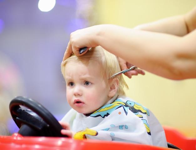 Nettes kleinkindkind, das seinen ersten haarschnitt erhält Premium Fotos