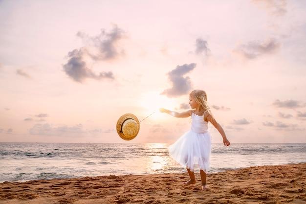 Nettes kleinkindmädchen mit dem blonden haar in einem weißen ballettröckchenkleid gehend auf einen sandigen strand bei sonnenuntergang. Premium Fotos