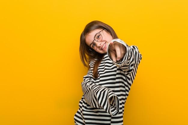 Nettes lächeln des kleinen kaukasischen netten mädchens pointingfront. Premium Fotos