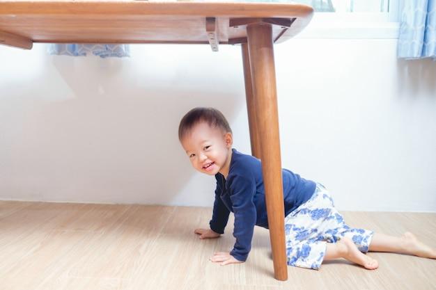 Nettes lächelndes lustiges kleines asiatisches kleinkind-jungenkind mit 18 monaten / 1-jährigem, das zu hause unter der tabelle betrachtet kamera spielt, kind hat spielerischen ausdruck auf seinem gesicht, glückliches kindheitskonzept Premium Fotos