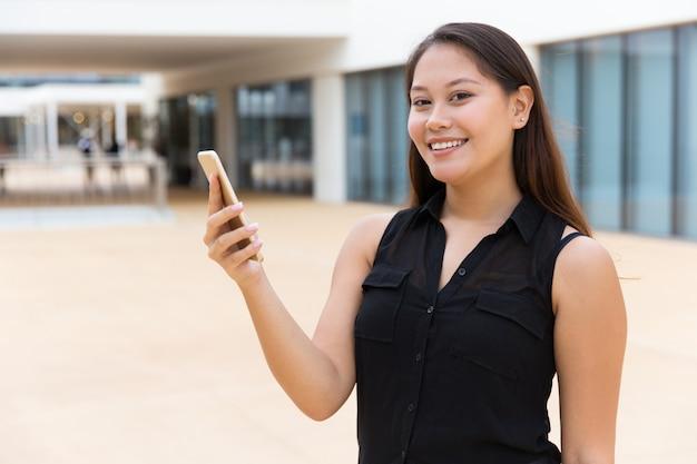 Nettes lächelndes studentenmädchen, das online-app verwendet Kostenlose Fotos