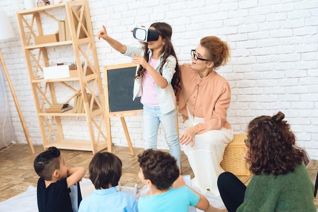Nettes mädchen betrachtet in gläser der virtuellen realität klassenzimmer. Premium Fotos
