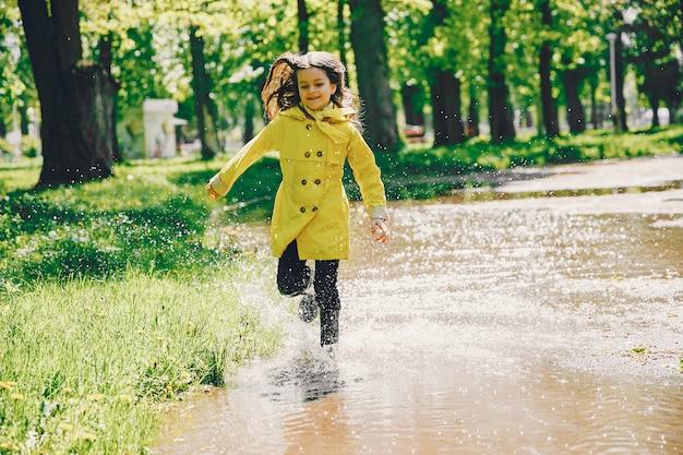 Nettes mädchen, das an einem regnerischen tag plaiyng ist Kostenlose Fotos