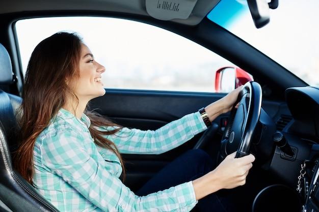 Nettes mädchen, das blaues hemd trägt, das im neuen automobil sitzt, glücklich, im verkehr stecken bleibt, musik hört, porträt. Premium Fotos