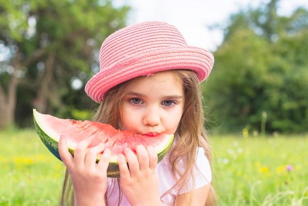 Nettes mädchen, das den rosa hut isst wassermelonenscheibe im park trägt Kostenlose Fotos