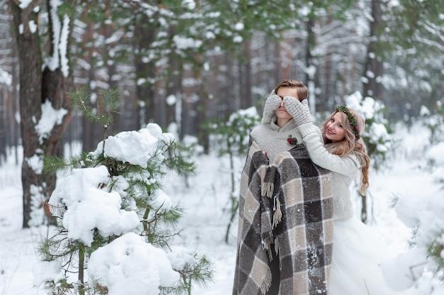Nettes mädchen, das die augen des freundes durch ihre gestrickten handschuhe bedeckt. winterhochzeit. Premium Fotos