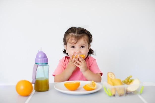 Nettes mädchen, das ihre orangen sitzt und genießt Kostenlose Fotos