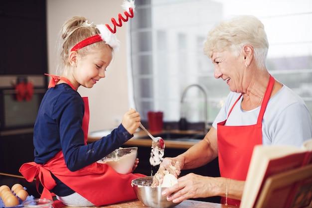 Nettes mädchen, das mit hilfe ihrer großmutter kocht Kostenlose Fotos