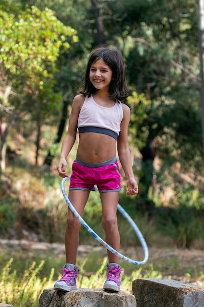 Nettes mädchen, das mit hula hoop aufwirft Premium Fotos