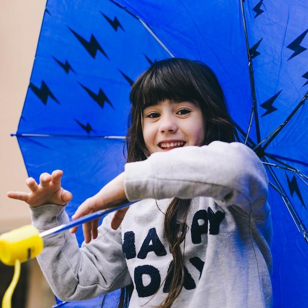 nettes mädchen das mit regenschirm spielt  kostenlose foto