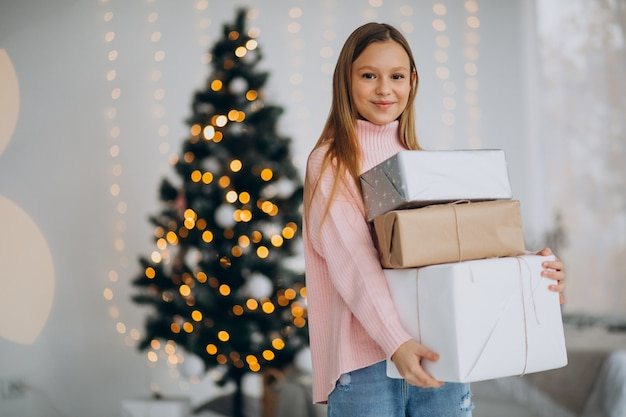 Nettes mädchen, das weihnachtsgeschenke durch weihnachtsbaum hält Kostenlose Fotos