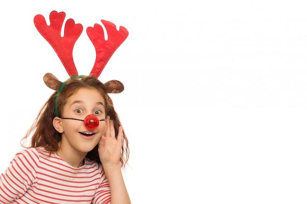 Nettes mädchen, das weihnachtsgeweihe und rote wekzeugspritze trägt Premium Fotos