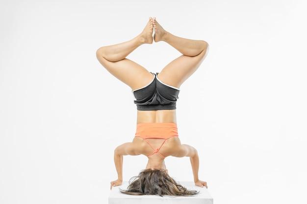 Nettes mädchen, das yoga auf weiß lokalisiert tut Premium Fotos