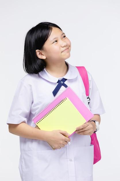 Nettes mädchen in der uniform des studenten mit briefpapier auf grau Premium Fotos