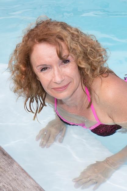 Nettes mädchen ist an einem swimmingpool im sommer entspannend Premium Fotos