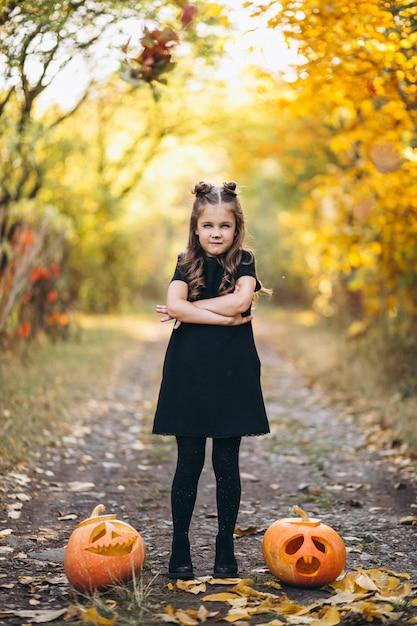 Nettes mädchen kleidete im halloween-kostüm draußen mit kürbisen an Kostenlose Fotos