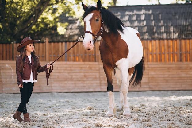 Nettes mädchen mit pferd an der ranch Kostenlose Fotos