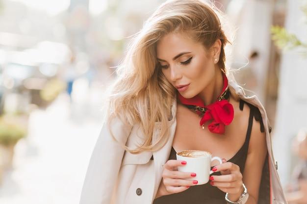 Nettes mädchen mit trendigem make-up, das an sonnigem tag entspannt und latte mit geschlossenen augen trinkt. außenporträt der herrlichen gebräunten frau mit blondem haar, das im mantel mit tasse kaffee aufwirft. Kostenlose Fotos