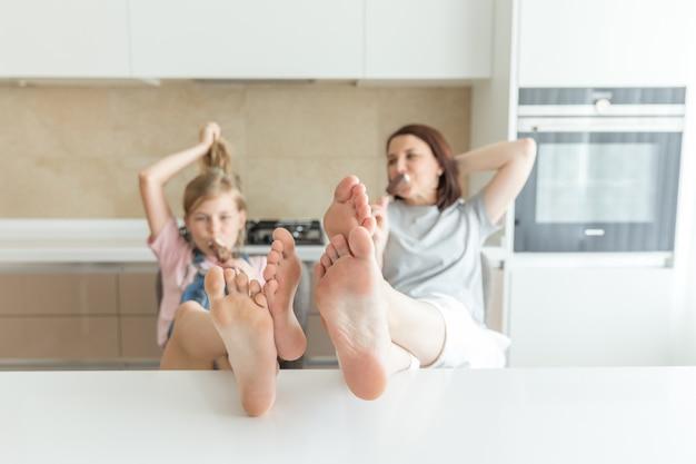 Nettes mädchen und ihre mutter lächeln beim essen der eiscreme in der küche mit den beinen auf einer tabelle Premium Fotos