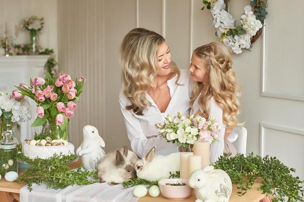 Nettes mädchen und mutter spielen mit kaninchen Premium Fotos